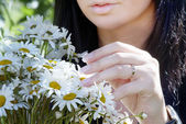 A girl gets on the hip the bouquet of camomiles — Stock Photo
