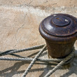 Stock Photo: Old rusty bollard with ropes