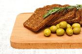 Brood, groene olijven en rozemarijn en bestuur — Stockfoto