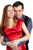 Young man embraces beautiful woman in red. — Stock Photo