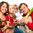 Cheerful young family with vegetables - Stock Photo
