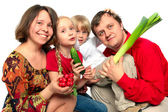 Cheerful young family with vegetables — Stock Photo