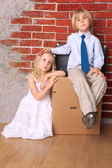 Beautiful tired children sitting on suitcases — Stock Photo
