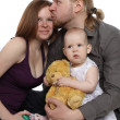 Happy family: dad holds baby in her arms and kisses her mother — Stock Photo