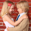 Stock Photo: Little boy hugging pretty girl. Love concept. Background