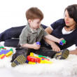 Devoted mother playing with colored blocks with her curious son — Stock Photo