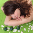 Young beautiful woman in spa center over green - Stock Photo