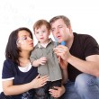 Happy family having fun. Father, mother and child blow bubbles. — Stock Photo