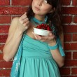 Beautiful brunette woman in blue summer dress eating cherry — Stock Photo