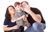 Happy family having fun. Man, woman and child blow bubbles. Seri — Stock Photo