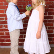 Stock Photo: Little boy gives girl beautiful bouquet of flowers. Love con