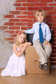 Boy and girl sitting on a cardboard box and a suitcase. Move — Stock Photo
