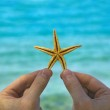 Starfish in hand on sea background — Stock Photo