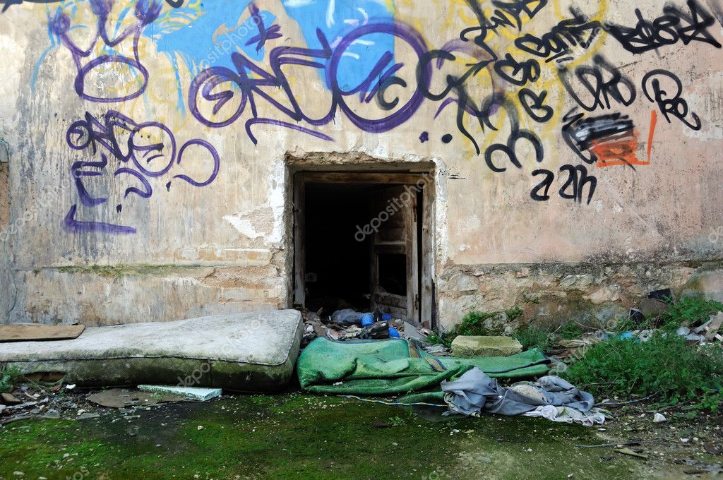 Dirty mattress and wooden pillow next to an abandoned house basement door. — Stock Photo #2742284