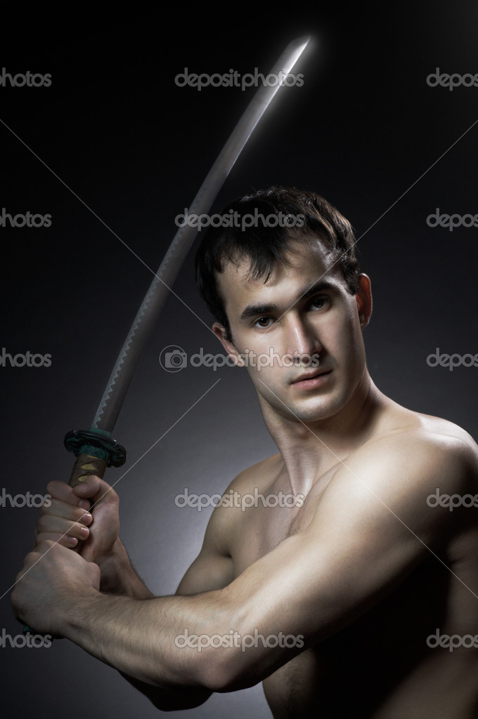 Man training with blade on black background  Stock Photo #2819559