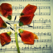 Music notes with the fallen petal — Stock Photo