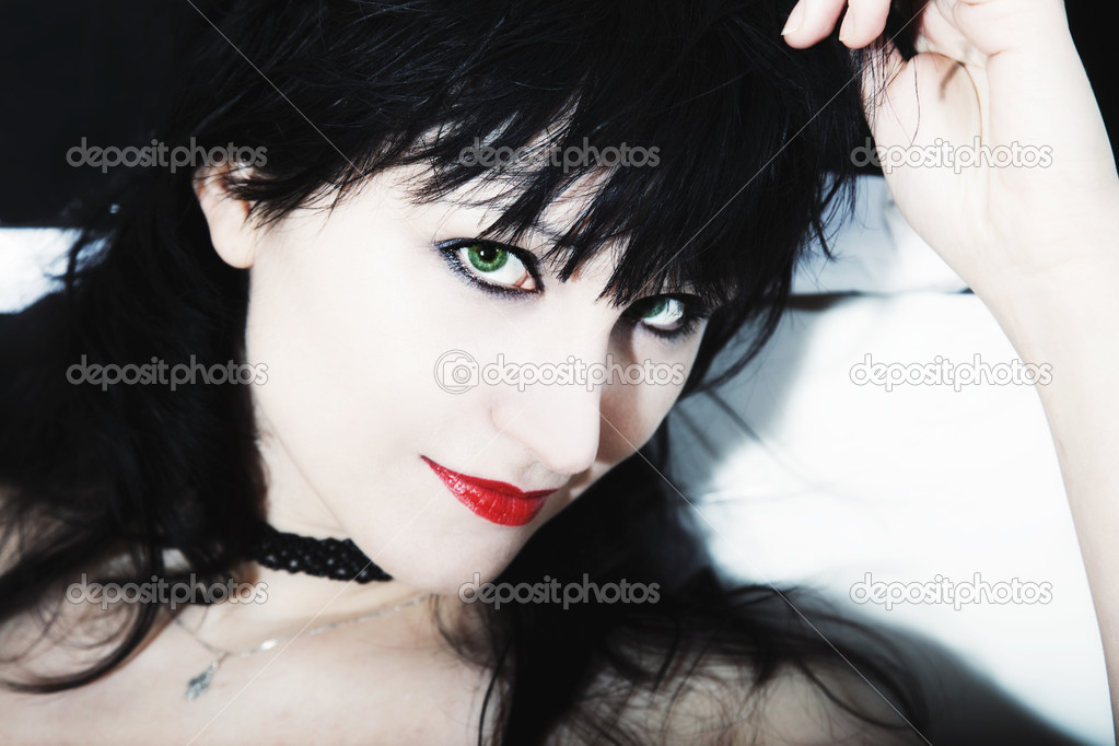 Young woman's face with black hair, red lips and green eyes — Stock Photo #3119590