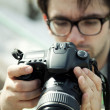 Young man in spectacles with camera — Stock Photo