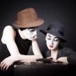 Two mimes in hats with a suitcase — Stock Photo