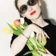 Young stylish woman wearing sunglasses with a bouquet of tulips on light background — Stock Photo #3385745