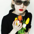 Young stylish woman wearing sunglasses with a bouquet of tulips — Stock Photo