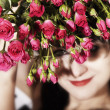 Brunette woman with a bouquet of pink roses — Stock Photo