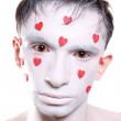 Young man with white makeup and red hearts instead of tears - Stock Photo