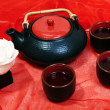 Ceramic teapot with cups and a white rose on a red cloth - Stock Photo