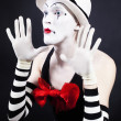 Mime with red bow ina white hat and striped gloves — Stock Photo