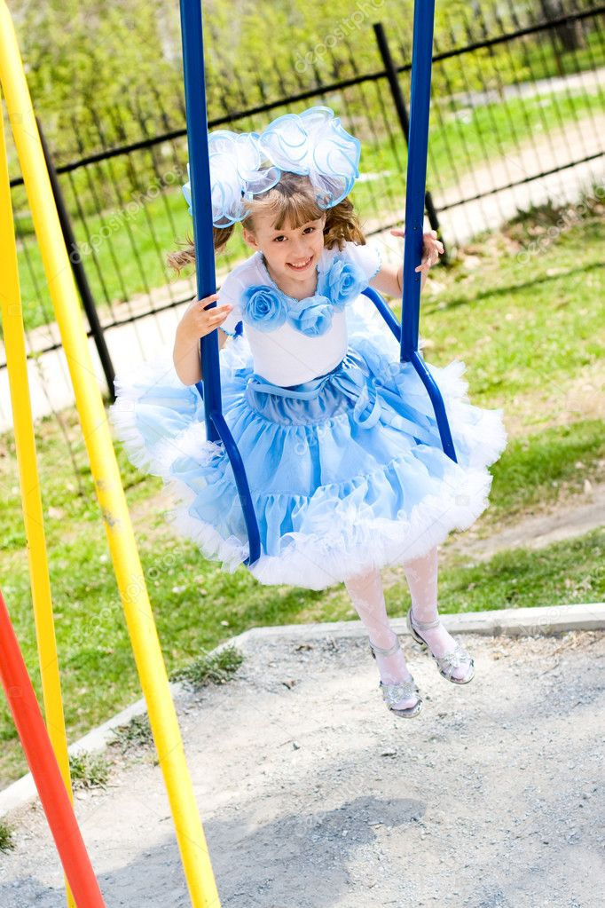 The little girl in holiday attire swing — Stock Photo #3312784