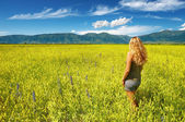 Girl in blooming field — Stock Photo