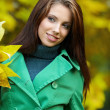 Fashion woman in autumn park holding yellow leaf — Stock Photo #3193399