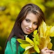 Fashion woman in autumn park holding yellow leaf — Stock Photo #3193426