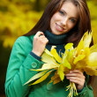 Fashion woman in autumn park holding yellow leaf — Stock Photo #3193437