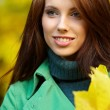 Fashion woman in autumn park holding yellow leaf — Stock Photo #3193463