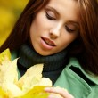 Fashion woman in autumn park holding yellow leaf — Stock Photo #3193473