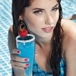 Woman with drink in swimming pool — Stock Photo #3460333