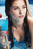 Woman with drink in swimming pool — Stok fotoğraf