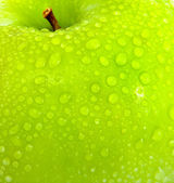 Apple in green with water drops — Stock Photo