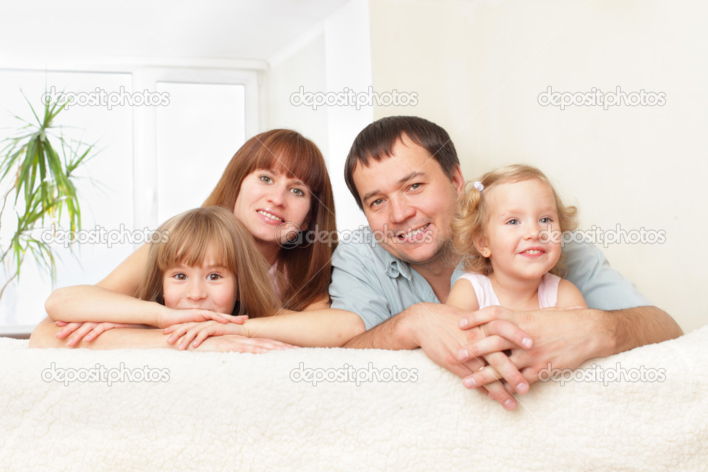 Happy family with two children on sofa — Stock Photo #2839750