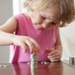 Girl putting coins — Stock Photo