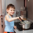 Child cooking porridge — Stock Photo