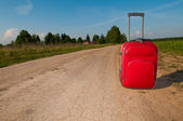 Suitcase on road — Stock fotografie