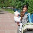 My mother carries a child in her arms and rolls the stroller in — Stock Photo
