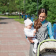 My mother carries a child in her arms and rolls the stroller in — Stock Photo #3516372