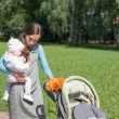 My mother carries a child in her arms and rolls the stroller in — Stock Photo #3516377