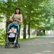 A young mother walking with a baby carriage in the park — Stock Photo