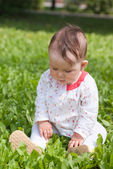 A little girl sitting on green grass in the park — Stock Photo