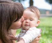 Mom kisses her little daughter, played in the park — Stock Photo