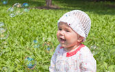 A little girl sitting on green grass in the park looking at soap — Stock Photo